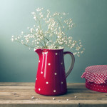 Beautiful flowers in red jug on wooden table